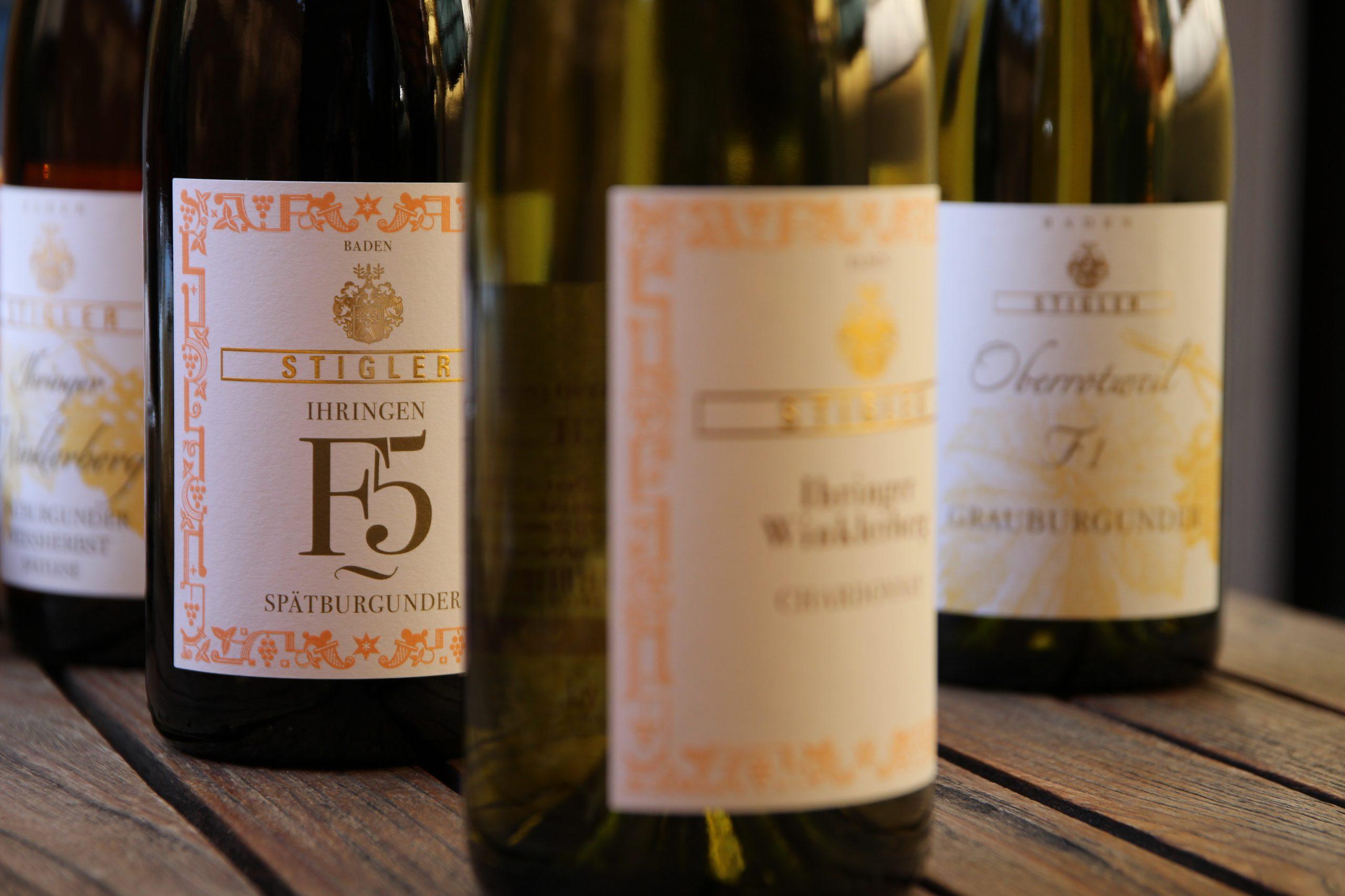 Drei Weinflaschen stehen im grünen Weinberg