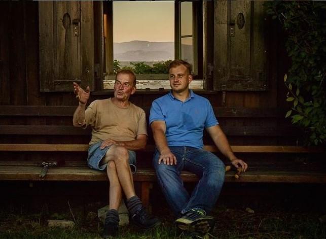 Papa und Sohn beim Weinprobieren im Keller
